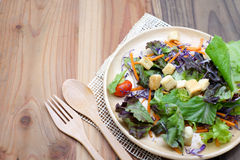 Φρέσκια σαλάτα στο ξύλινο πιάτο στον ξύλινο πίνακα στοκ εικόνες