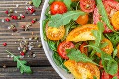 Φρέσκια σαλάτα των κόκκινων, ρόδινων και κίτρινων ντοματών με το arugula Στοκ Φωτογραφία