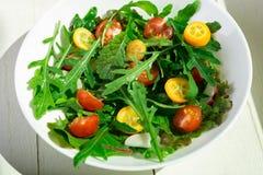 Φρέσκια σαλάτα arugula με το κεράσι κουμκουάτ και ντοματών στο άσπρο ξύλινο υπόβαθρο Τοπ όψη τρόφιμα υγιή σιτηρέσιο Στοκ Φωτογραφία