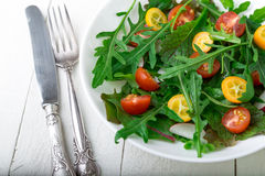 Φρέσκια σαλάτα arugula με το κεράσι κουμκουάτ και ντοματών στο άσπρο ξύλινο υπόβαθρο Τοπ όψη τρόφιμα υγιή σιτηρέσιο Στοκ Εικόνα