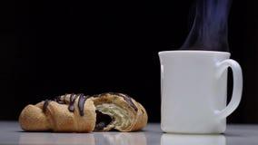 Φρέσκια σοκολάτα croissant και φλυτζάνι του καυτού καφέ με τον ατμό σε έναν άσπρο πίνακα στο μαύρο υπόβαθρο φιλμ μικρού μήκους