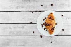 Φρέσκια σοκολάτα croissant στο πιάτο πέρα από τον αγροτικό ξύλινο πίνακα dela στοκ εικόνα