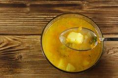 Φρέσκια σούπα μπιζελιών στο κύπελλο γυαλιού στον πίνακα Κουτάλι με τη σούπα Στοκ Εικόνες