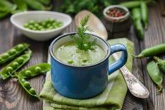 Φρέσκια σούπα πράσινων μπιζελιών με τους σπόρους μπιζελιών και τους λοβούς μπιζελιών Στοκ Φωτογραφία