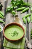 Φρέσκια σούπα πράσινων μπιζελιών με τους σπόρους μπιζελιών και τους λοβούς μπιζελιών Στοκ εικόνα με δικαίωμα ελεύθερης χρήσης