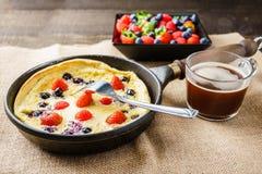 Φρέσκια σπιτική ολλανδική τηγανίτα μωρών με το σμέουρο βακκινίων και φράουλα σε ένα τηγάνι σε έναν πίνακα Στοκ Φωτογραφίες
