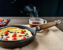 Φρέσκια σπιτική ολλανδική τηγανίτα μωρών με το σμέουρο βακκινίων και φράουλα σε ένα τηγάνι σε έναν πίνακα Στοκ εικόνες με δικαίωμα ελεύθερης χρήσης