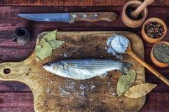 Φρέσκια τήξη ψαριών για το μαγείρεμα σε έναν πίνακα κουζινών Στοκ Εικόνες