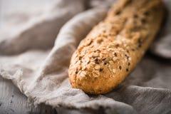 Φρέσκια, υγιής ολόκληρη φραντζόλα σίκαλης σιταριού στο ύφασμα και αγροτικός ξύλινος πίνακας Στοκ Φωτογραφίες