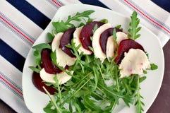 Φρέσκια υγιής vegan σαλάτα με το πράσινο arugula και τα κόκκινα παντζάρια και μοτσαρέλα στο άσπρο πιάτο στο ύφασμα Στοκ εικόνα με δικαίωμα ελεύθερης χρήσης