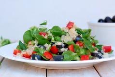 Φρέσκια υγιής vegan σαλάτα με quinoa, σαλάτα καλαμποκιού, μαύρες ελιές, κόκκινο πιπέρι και ελαιόλαδο στο άσπρο ύφασμα πιάτων στη  Στοκ Εικόνες