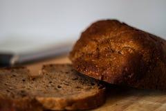 Φρέσκια φέτα ψωμιού και τέμνον μαχαίρι στον αγροτικό πίνακα στοκ εικόνα με δικαίωμα ελεύθερης χρήσης