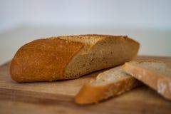 Φρέσκια φέτα ψωμιού και τέμνον μαχαίρι στον αγροτικό πίνακα στοκ φωτογραφία με δικαίωμα ελεύθερης χρήσης