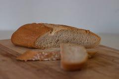 Φρέσκια φέτα ψωμιού και τέμνον μαχαίρι στον αγροτικό πίνακα στοκ εικόνες