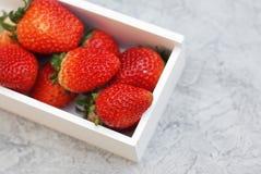 Φρέσκια φράουλα μούρων στο ξύλινο άσπρο κιβώτιο με τα πράσινα φρούτα συγκομιδών φύλλων η ανασκόπηση απομόνωσε το λευκό διάστημα α Στοκ Εικόνες