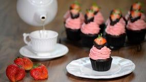 Φρέσκια φράουλα σοκολάτας cupcake με ένα φλυτζάνι του τσαγιού απόθεμα βίντεο