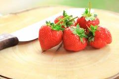 Φρέσκια φράουλα, γλυκά φρούτα, στον ξύλινο τεμαχίζοντας πίνακα με το μαχαίρι Στοκ Εικόνες