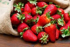 Φρέσκια φράουλα burlap στο σάκο στο ξύλο Στοκ Εικόνες
