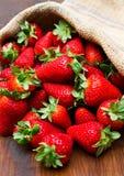 Φρέσκια φράουλα burlap στο σάκο στο ξύλο Στοκ Φωτογραφίες