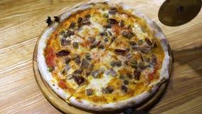 Φρέσκια ψημένη πίτσα που κόβεται στις φέτες με τον κόπτη πιτσών φιλμ μικρού μήκους