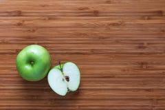 Φρέσκια ώριμη πράσινη Γιαγιά Σμίθ μήλων: ολόκληρος και τεμαχισμένος στο μισό σε έναν ξύλινο τέμνοντα πίνακα Έννοια φρούτων φύσης Στοκ Εικόνες