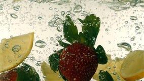 Φρέσκια ώριμη πτώση μούρων και φρούτων στο μεταλλικό νερό, σε αργή κίνηση φιλμ μικρού μήκους