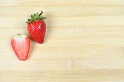 Φρέσκια Juicy φράουλα και μια περικοπή φετών που απομονώνεται στο ξύλινο υπόβαθρο στοκ φωτογραφίες