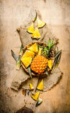 Φρέσκοι ανανάδες, ολόκληρος και τεμαχισμένος σε ένα καλάθι στο παλαιό ύφασμα Στοκ εικόνες με δικαίωμα ελεύθερης χρήσης