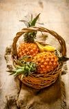 Φρέσκοι ανανάδες στο καλάθι ρηχός πίνακας πεδίων βάθους ξύλινος Στοκ Φωτογραφίες