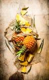 Φρέσκοι ανανάδες στο καλάθι ρηχός πίνακας πεδίων βάθους ξύλινος Στοκ Φωτογραφία