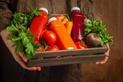 Φρέσκοι καταφερτζήδες χυμού από τις διάφορες ντομάτες τεύτλων μήλων καρότων λαχανικών στα μπουκάλια σε ένα ξύλινο κιβώτιο στα θηλ στοκ εικόνες