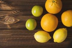Φρέσκοι λεμόνια, ασβέστες και πορτοκάλια στον καφετή ξύλινο πίνακα Juicy fru Στοκ Εικόνες