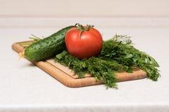 Φρέσκοι ντομάτα, αγγούρι, μαϊντανός και άνηθος στον τέμνοντα πίνακα Στοκ Φωτογραφίες