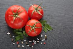 Φρέσκοι ντομάτες, καρυκεύματα και μαϊντανός στη μαύρη πέτρα Στοκ εικόνα με δικαίωμα ελεύθερης χρήσης