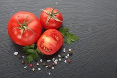 Φρέσκοι ντομάτες, καρυκεύματα και μαϊντανός στη μαύρη πέτρα Στοκ Εικόνες