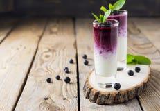 Φρέσκοι υγιείς καταφερτζήδες βακκινίων σε ένα γυαλί με τα μούρα και τα φύλλα μεντών σε μια ξύλινη στάση Στοκ φωτογραφία με δικαίωμα ελεύθερης χρήσης