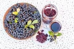 Φρέσκοι χυμός και μαρμελάδα του μαύρου chokeberry melanocarpa Aronia στο γυαλί και του μούρου στο δοχείο στο άσπρο κατασκευασμένο Στοκ εικόνες με δικαίωμα ελεύθερης χρήσης