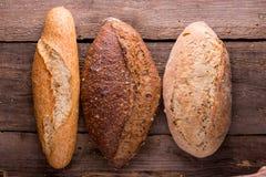 Φρέσκοι ψωμί και σίτος στον ξύλινο στοκ φωτογραφία