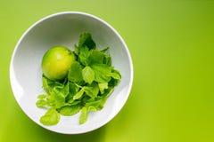 Φρέσκος ασβέστης με τη μέντα στο άσπρο φλυτζάνι σε πράσινο Στοκ Φωτογραφίες