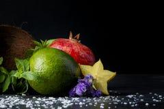 Φρέσκος γρανάτης, ολόκληρα αβοκάντο και carambola Χαριτωμένες λουλούδια και καρύδα Κινηματογράφηση σε πρώτο πλάνο των φρούτων σε  Στοκ εικόνα με δικαίωμα ελεύθερης χρήσης