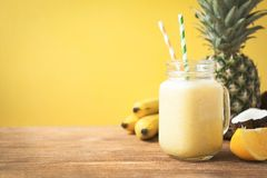 Φρέσκος εξωτικός καταφερτζής με τα φρούτα και γάλα καρύδων στο κίτρινο υπόβαθρο στοκ φωτογραφίες