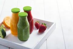 Φρέσκος καταφερτζής φραουλών, πορτοκαλιών και μπρόκολου στα μπουκάλια με τα φρούτα και λαχανικά σε ένα άσπρο ξύλινο αγροτικό υπόβ Στοκ φωτογραφία με δικαίωμα ελεύθερης χρήσης