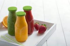Φρέσκος καταφερτζής φραουλών, πορτοκαλιών και μπρόκολου στα μπουκάλια με τα φρούτα και λαχανικά σε ένα άσπρο ξύλινο αγροτικό υπόβ Στοκ Εικόνες