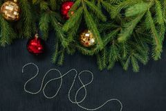 Φρέσκος κλάδος έλατου με τα παιχνίδια Χριστουγέννων Όμορφο υπόβαθρο για να παρεμβάλει το κείμενο κορυφαία όψη Ξύλινο υπόβαθρο σχε Στοκ εικόνα με δικαίωμα ελεύθερης χρήσης