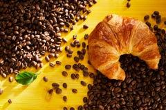 Φρέσκος λεπιοειδής croissant στα ψημένα φασόλια καφέ στοκ εικόνα με δικαίωμα ελεύθερης χρήσης