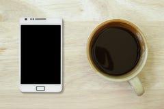 Φρέσκος μαύρος καφές σε ένα κεραμικό φλυτζάνι σε έναν ξύλινους πίνακα και τη Mobil Στοκ Εικόνες