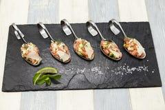 Φρέσκος νορβηγικός σολομός ταρτάρου σε ένα μικρό κουτάλι σε ένα μαύρο πιάτο Στοκ φωτογραφία με δικαίωμα ελεύθερης χρήσης