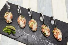 Φρέσκος νορβηγικός σολομός ταρτάρου σε ένα μικρό κουτάλι σε ένα μαύρο πιάτο Στοκ εικόνα με δικαίωμα ελεύθερης χρήσης