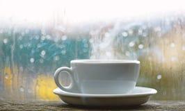 Φρέσκος παρασκευασμένος καφές στο άσπρο φλυτζάνι ή κούπα στο windowsill Υγρά παράθυρο γυαλιού και φλυτζάνι του καυτού καφέ Νεφελώ στοκ εικόνες