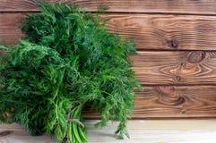 Φρέσκος πράσινος άνηθος βιταμινών στους καφετιούς πίνακες στοκ φωτογραφία